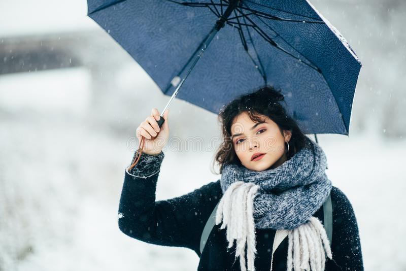 A cute young girl holds umbrellas in the hands of the winter season. Winter portrait of young beautiful brunette woman. A cute young girl holds umbrellas in the royalty free stock images