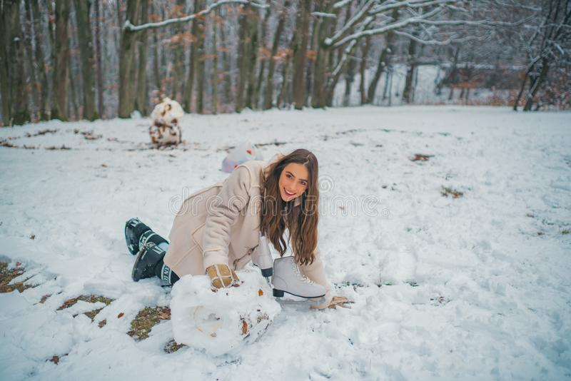 Winter portrait of young beautiful brunette woman in snow Garden. Snowing winter beauty fashion concept. royalty free stock photos