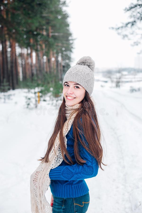 Winter portrait of young beautiful brunette woman wearing knitted snood covered in snow. Woman in winter forest stock photography