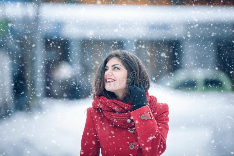 Winter portrait of young beautiful brunette woman wearing knitted snood and red coat covered in snow. Snowing winter beauty fashio stock photos