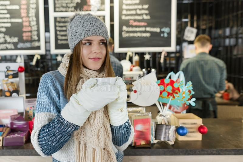Winter portrait of young beautiful woman with cup of coffee royalty free stock images