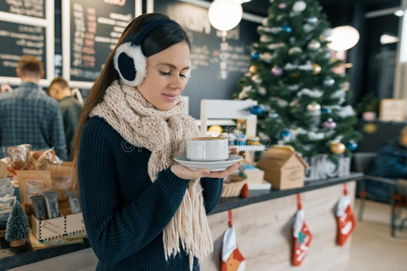 Winter portrait of young beautiful woman in knitted scarf, fur ears, warm sweater with cup of coffee. Girl near bar counter, royalty free stock photo