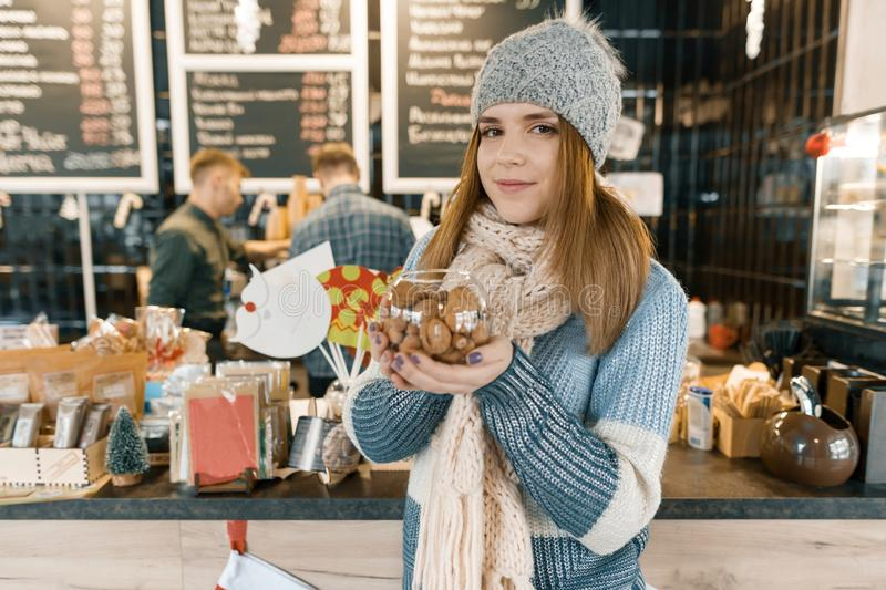 Winter portrait of young beautiful woman in knitted scarf, knitted hat, mittens, warm sweater with bowl of hazelnuts and walnuts stock image