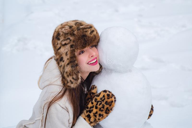 Winter portrait of young beautiful woman in snow Garden make snowman. Happy woman winter portrait. Happy winter time. royalty free stock photos