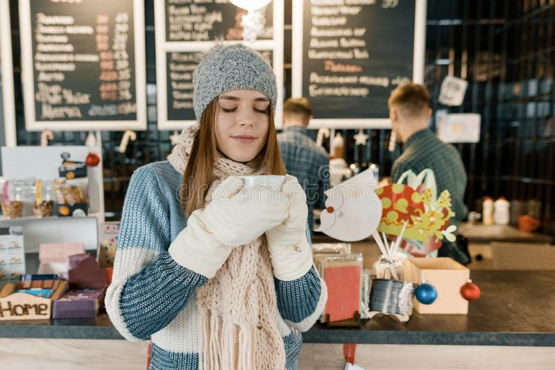 Winter portrait of young beautiful woman in knitted scarf, knitted hat, mittens, warm sweater with cup of coffee royalty free stock image
