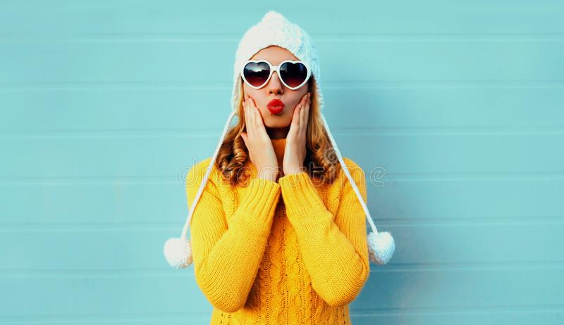 Winter portrait young woman blowing red lips sending sweet air kiss wearing yellow knitted sweater and white hat with pom pom royalty free stock images
