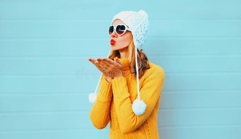 Winter portrait young woman blowing red lips sending sweet air kiss wearing yellow knitted sweater and white hat with pom pom royalty free stock image