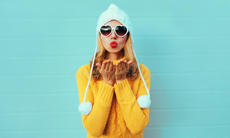 Winter portrait young woman blowing red lips sending sweet air kiss wearing yellow knitted sweater and white hat with pom pom royalty free stock photo