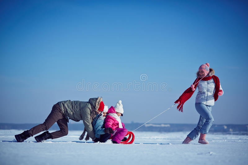 Winter recreation. Cute siblings and their parents spending winter weekend outdoors stock photography