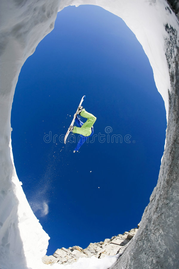 On winter resort. Below view of fearless sportsman jumping high over snow covered mountains on snowboard royalty free stock image
