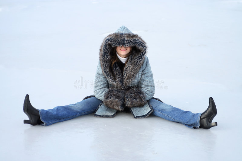 Winter rest. Young woman sits on the ice royalty free stock photo