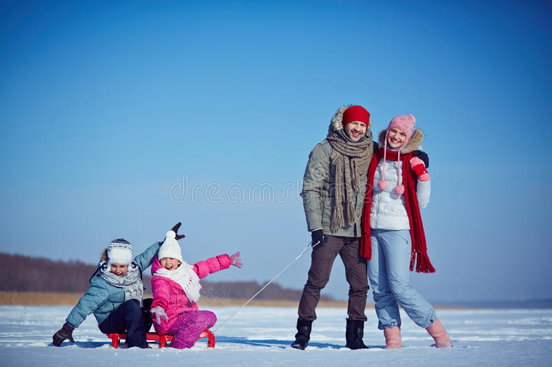 Winter rest. Cute siblings sitting on sledge with happy parents near by royalty free stock photo