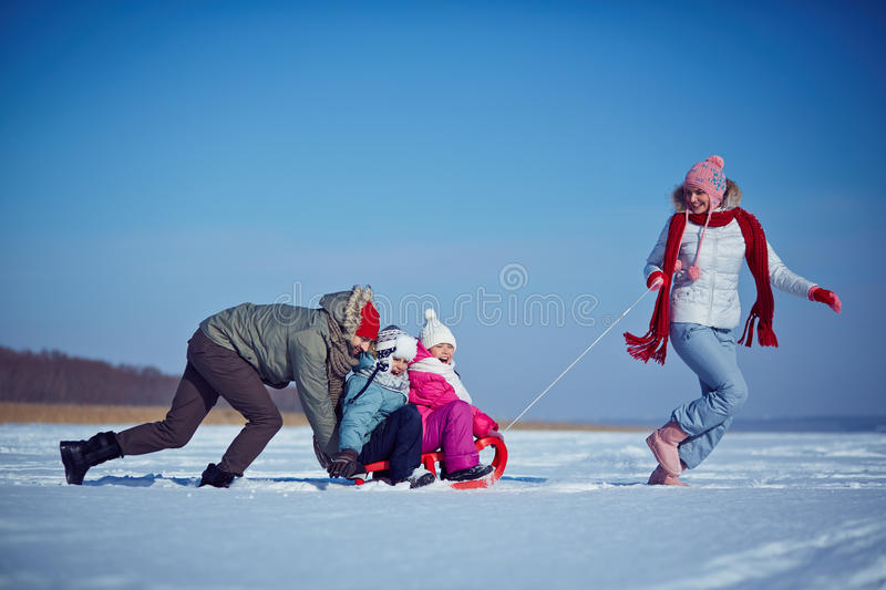 Winter ride. Cute kids and their parents riding on sledge on winter weekend stock photos