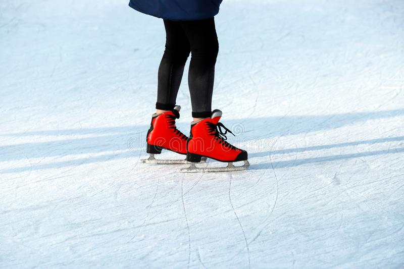 Winter rink. The girl in the red skates riding on the ice. Active family sport during the winter holidays and the cold season. stock image