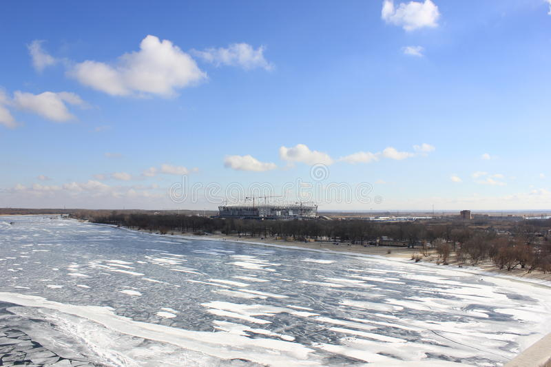 Winter river covered with ice with blue cloudy sky stock image