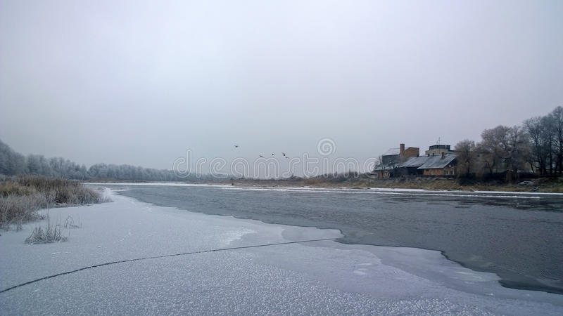 Winter river. The water surface is covered with ice. A crack in the ice. Winter graphics. Cold River reverie. The banks are covered with snow. Time for winter royalty free stock photos