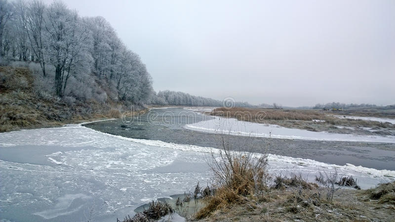 Winter river. The water surface is covered with ice. A crack in the ice. Winter graphics. Cold River reverie. The banks are covered with snow. Trees covered stock images