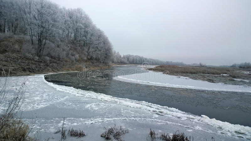 Winter river. The water surface is covered with ice. A crack in the ice. Winter graphics. Cold River reverie. The banks are covered with snow. Trees covered royalty free stock image