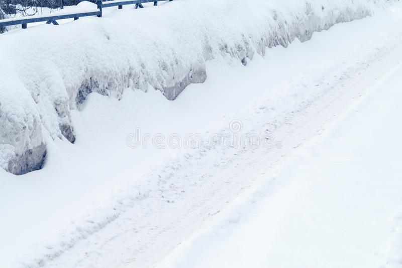 Winter road covered with snow, drifts on the side of the road royalty free stock photo