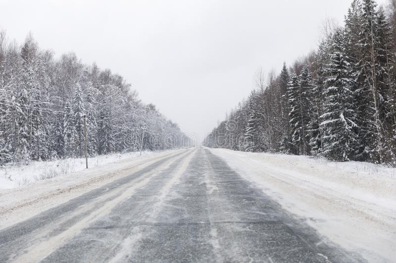 Winter road with ice on the asphalt, trees under snow during the winter frost. In Russia royalty free stock images