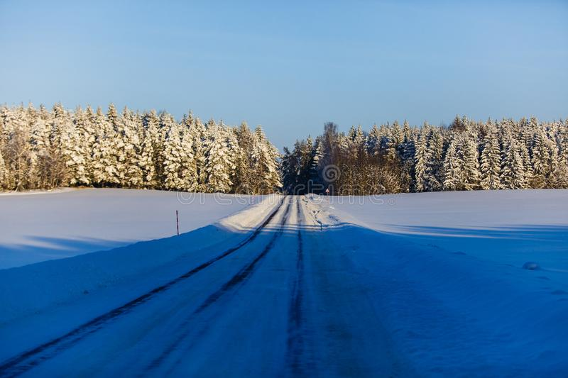 Winter road leading to snowy forest. Season landscape. After blizzard scenery royalty free stock photos