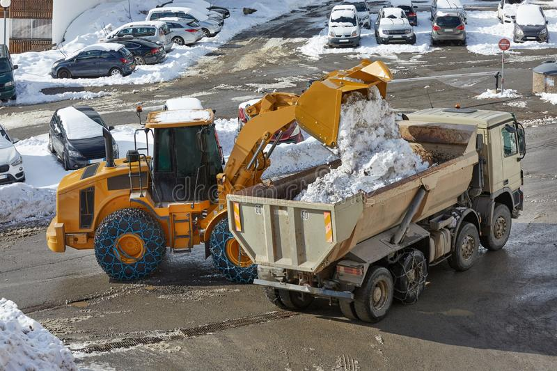 Winter road loader removing snow. Removing snow from the road, loading on a dump truck royalty free stock photography