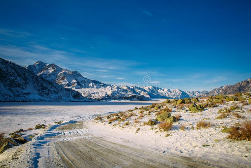 Winter road in the mountains. Rocky mountains are covered with snow against the blue sky in sunlight. Road trips to wild places.  royalty free stock photos