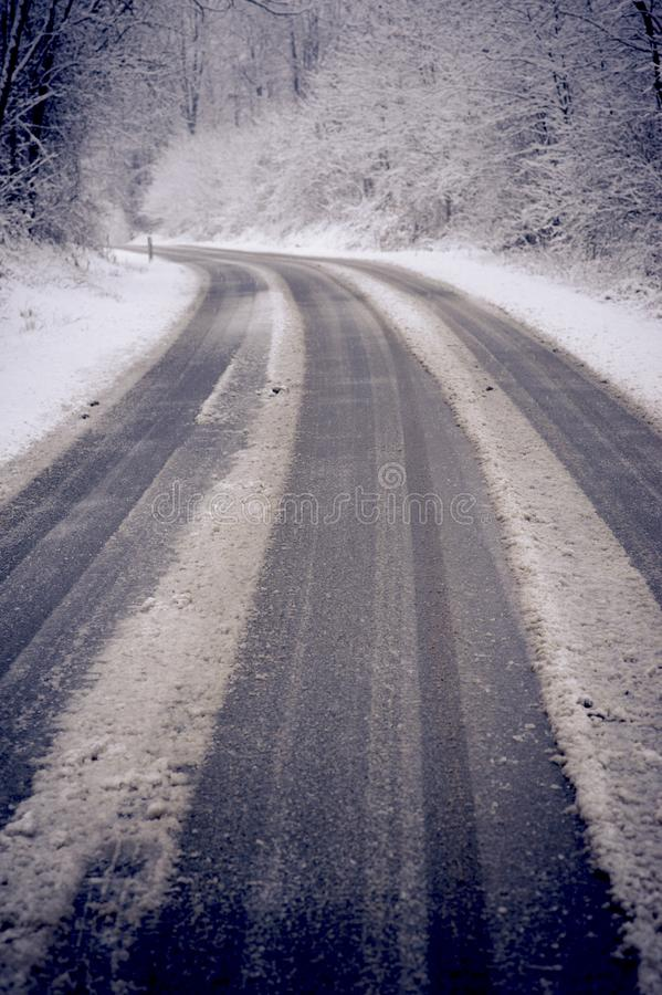 Winter road with snow. On the ground. travel in difficult way to enjoy the colder season. white image with black asphalt in contrast. drive and travel concept royalty free stock photos