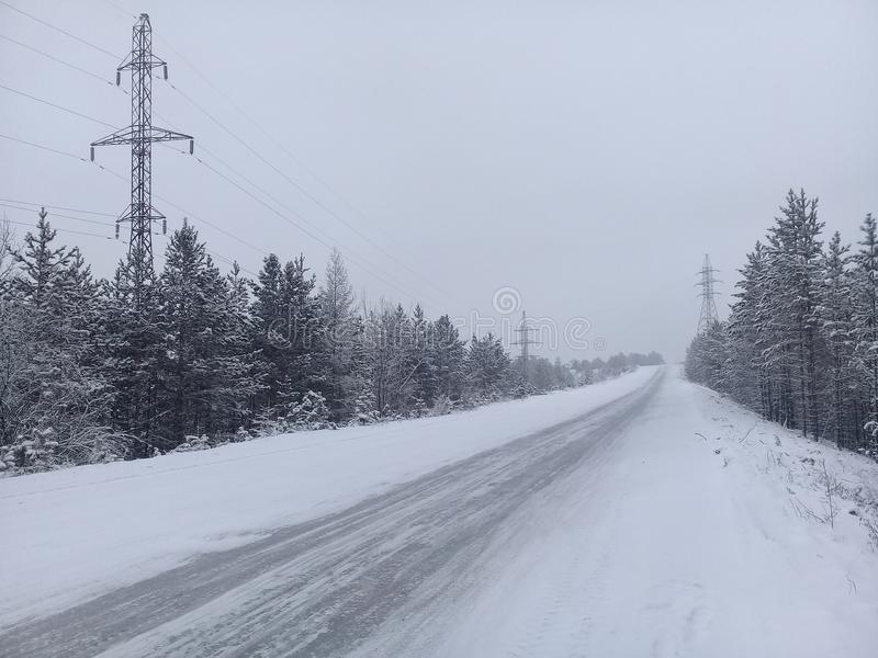 Winter road to the horizon. Accompanied by trees and a power line stock photo