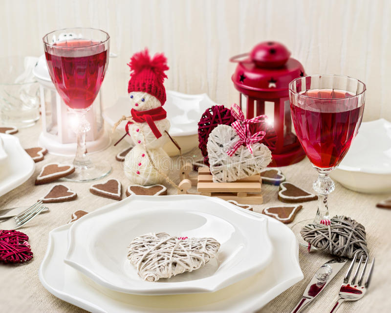 Winter romantic evening on Valentine's day. Valentine's day tabl. E setting with candles and decorations in the form of hearts royalty free stock photo