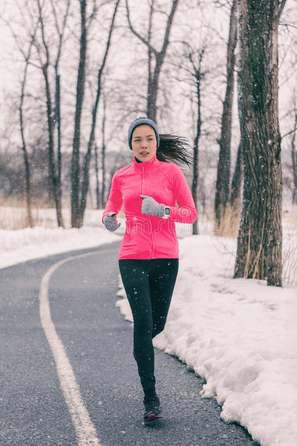 Winter exercise Asian woman running in cold weather clothes. Chinese runner girl training outside. Athlete working out jogging in royalty free stock photos
