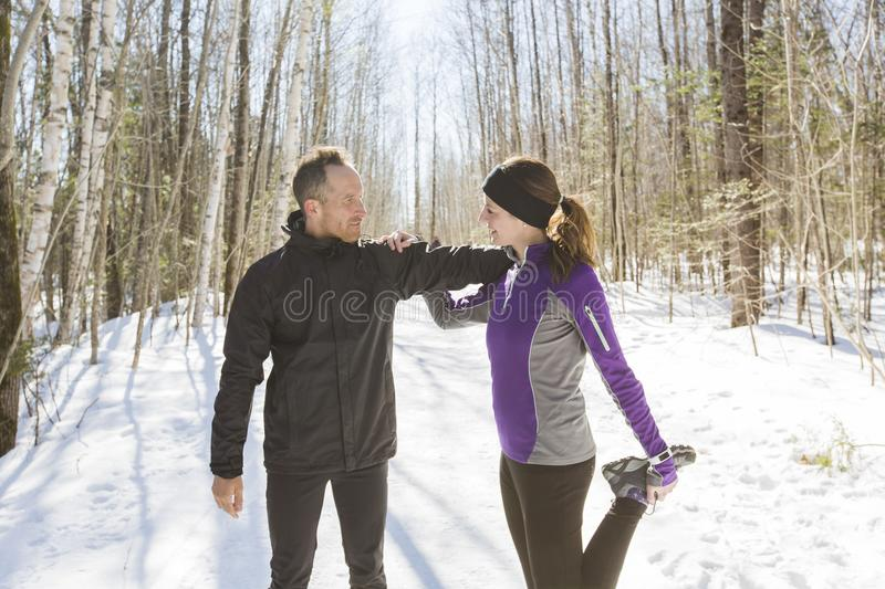 Winter running exercise couple. Runners jogging in snow. royalty free stock photography