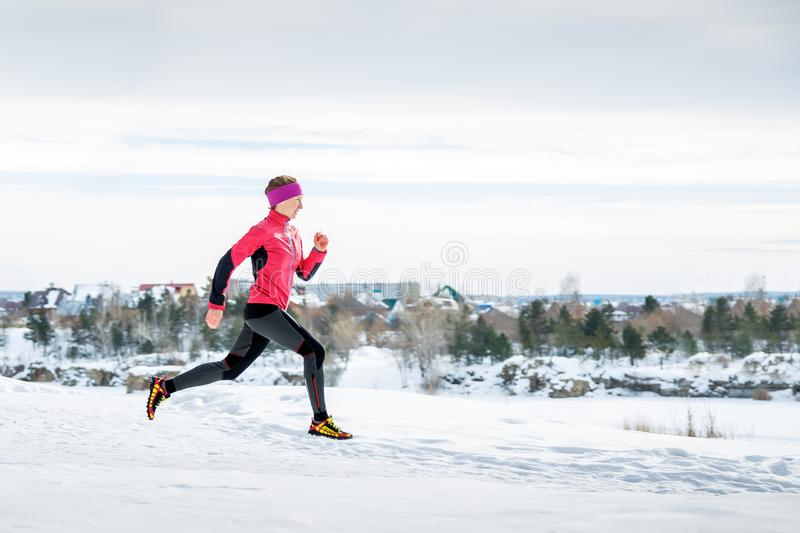 Winter running exercise. Runner jogging in snow. Young woman fitness model running in a city park stock images
