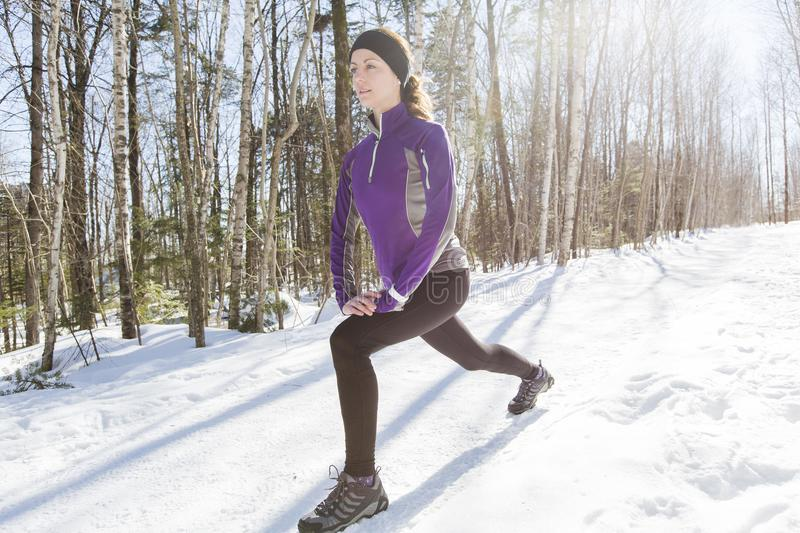 Winter running exercise. Runner jogging in snow. royalty free stock image