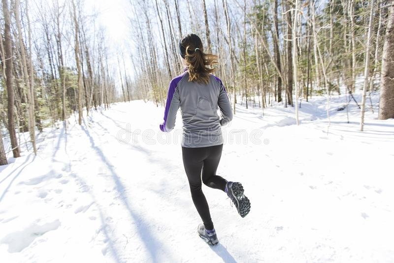Winter running exercise. Runner jogging in snow. stock photo