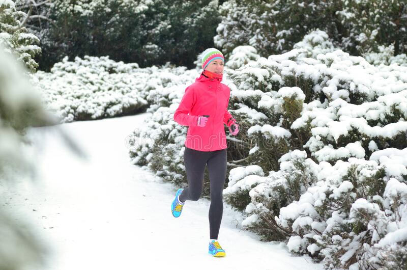 Winter running in park: happy woman runner jogging in snow, outdoor sport and fitness stock image