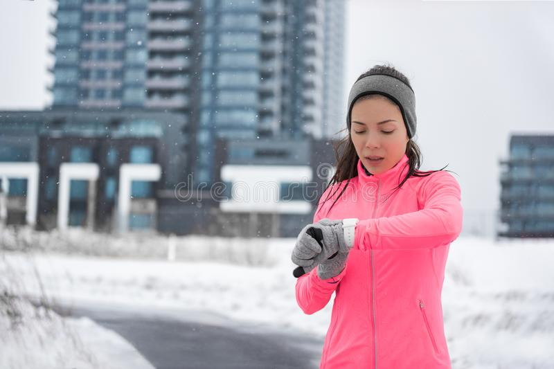 Winter running smartwatch fitness girl in cold snow weather jogging outside on street wearing smart watch and windproof clothes. With gloves, headband, pink stock photography