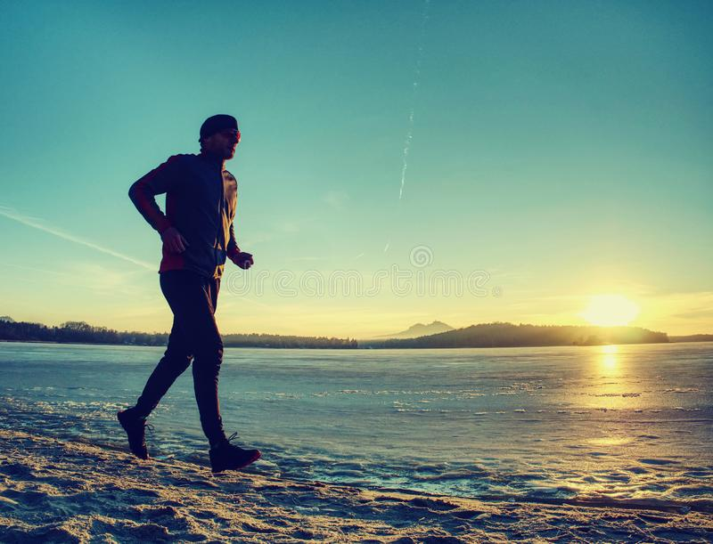 Winter running training. Middle age active person runner jogging stock photography