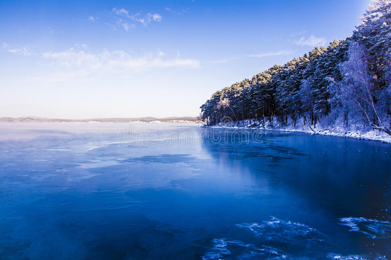Winter Russian lake - water, mist, snow forest and mountains stock images