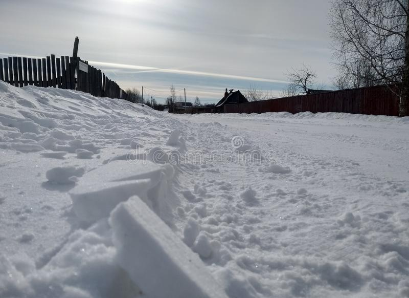 Winter in the Russian village morning.Blue frosty sky. Winter morning in the Russian village in the snow. On the horizon wooden fence and the old house. Blue stock photos