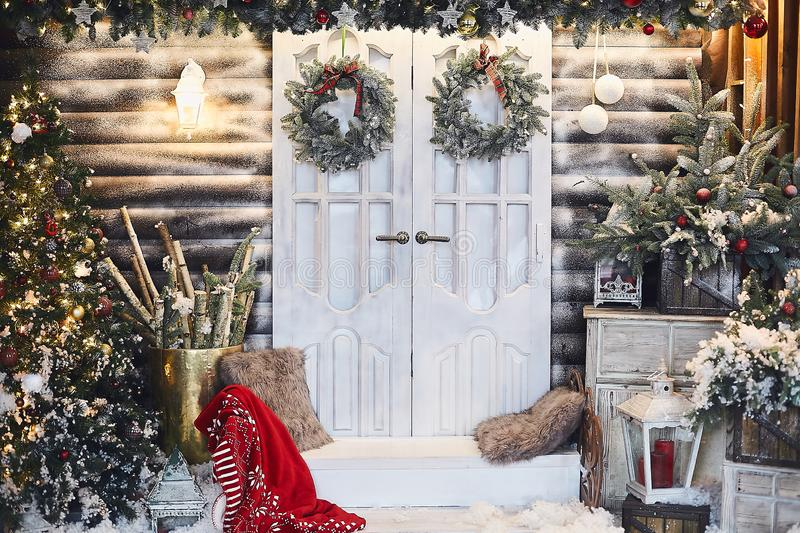 Winter rustic interior decorated for New year with artificial snow and Christmas tree. Winter exterior of a country. House with Christmas decorations in rustic royalty free stock image