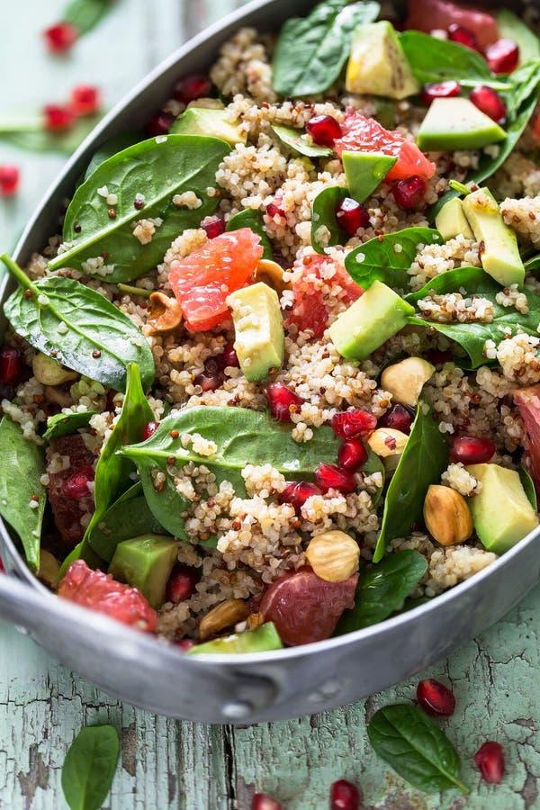 Winter-Salat mit Blutorange, Spinat, Granatapfel, Avocado, Quinoa, Haselnüssen und Bulgur lizenzfreies stockfoto