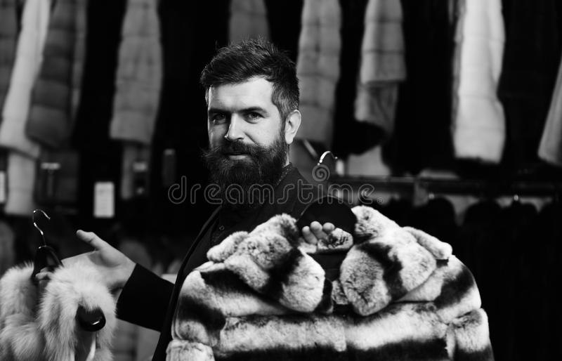 Winter sale. Guy with beard chooses furry coats. Shop assistant with expensive overcoats. Elegance and glamour concept royalty free stock photo