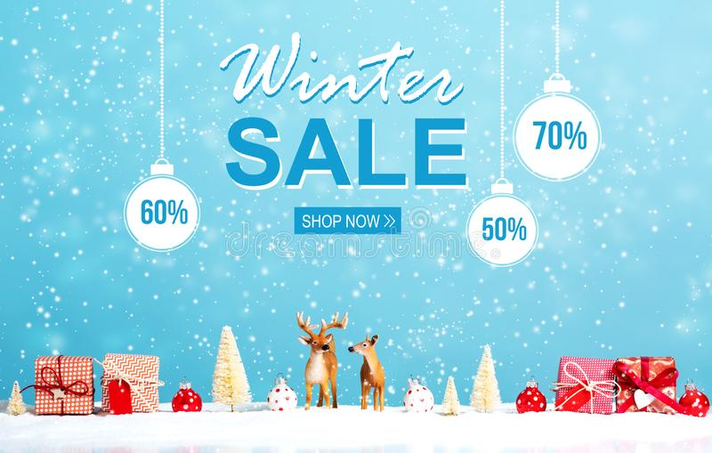 Winter sale message with reindeer and Christmas gifts. In snowy day royalty free stock images