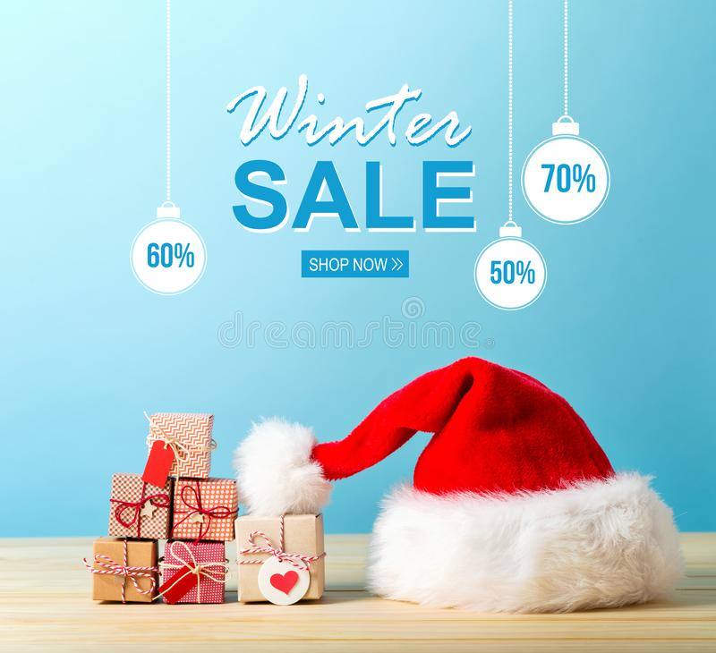 Winter sale message with a Santa hat and gift boxes. Winter sale message with a Santa hat and tiny Christmas gift boxes royalty free stock images