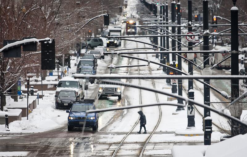 Winter in Salt Lake City on Light Rail Tracks. SALT LAKE CITY, UNITED STATES - Dec 28, 2012: A pedestrian walks along the crosswalk at the intersection of 200 S stock photography