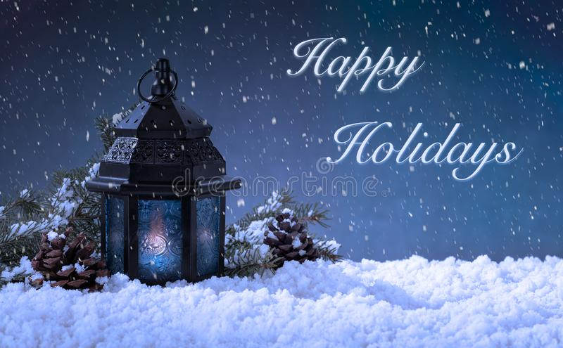 Christmas Scene With Happy Holidays Text. Winter scene of a burning lantern on snow against a snowy night sky with Happy Holidays text stock image
