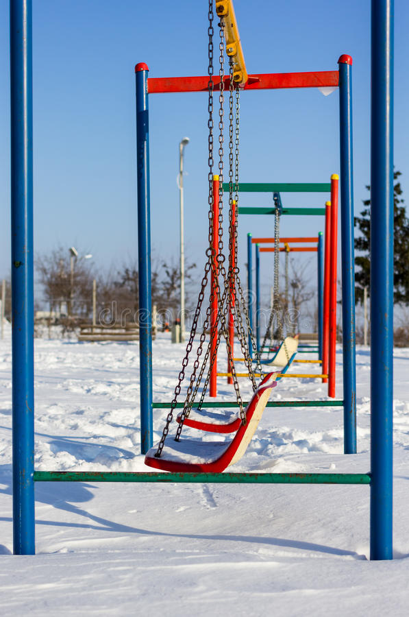 Winter scene with couple of swings in park. Sample stock photos