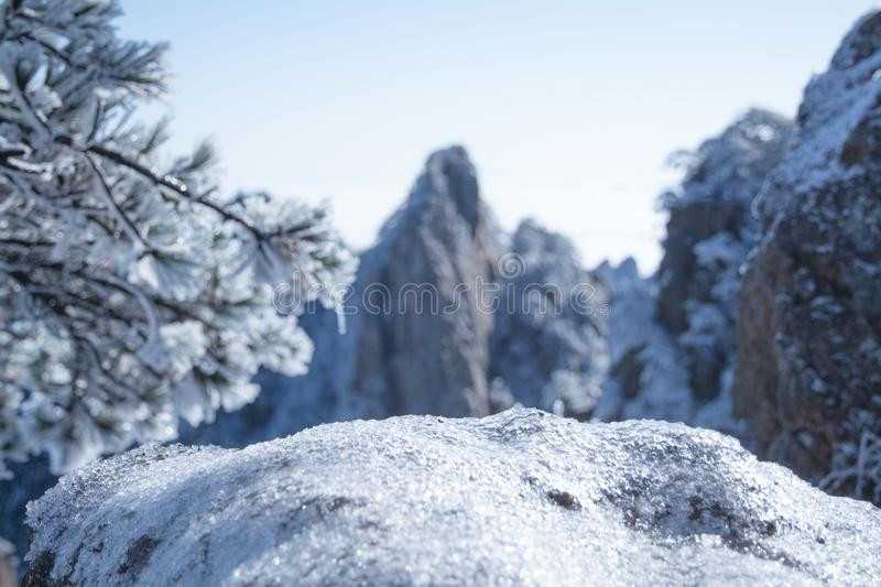 Winter scene with ice covered trees and mountain. In huang mountain of China. Close up for the stone covered by ice with blurred trees and mountain peak as royalty free stock image