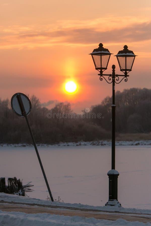Winter scene: lantern, sunset and broken landmark royalty free stock photos